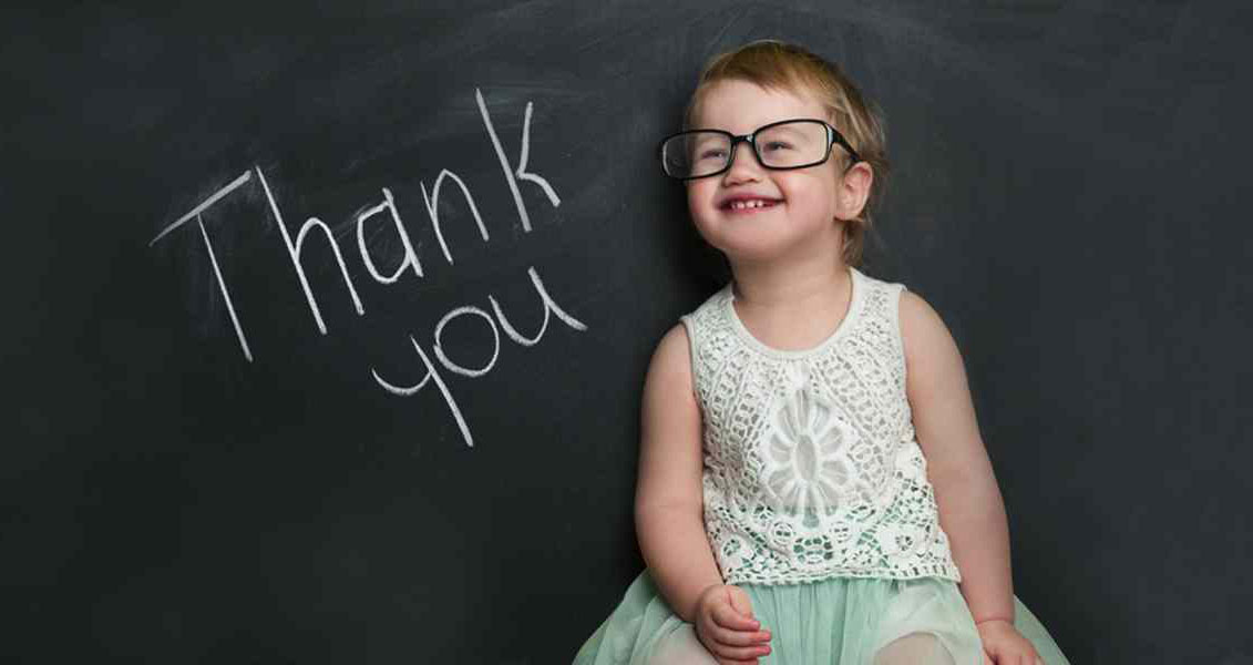 """young girl wearing glasses standing in front of a blackboard with the words """"Thank You"""" written on it"""