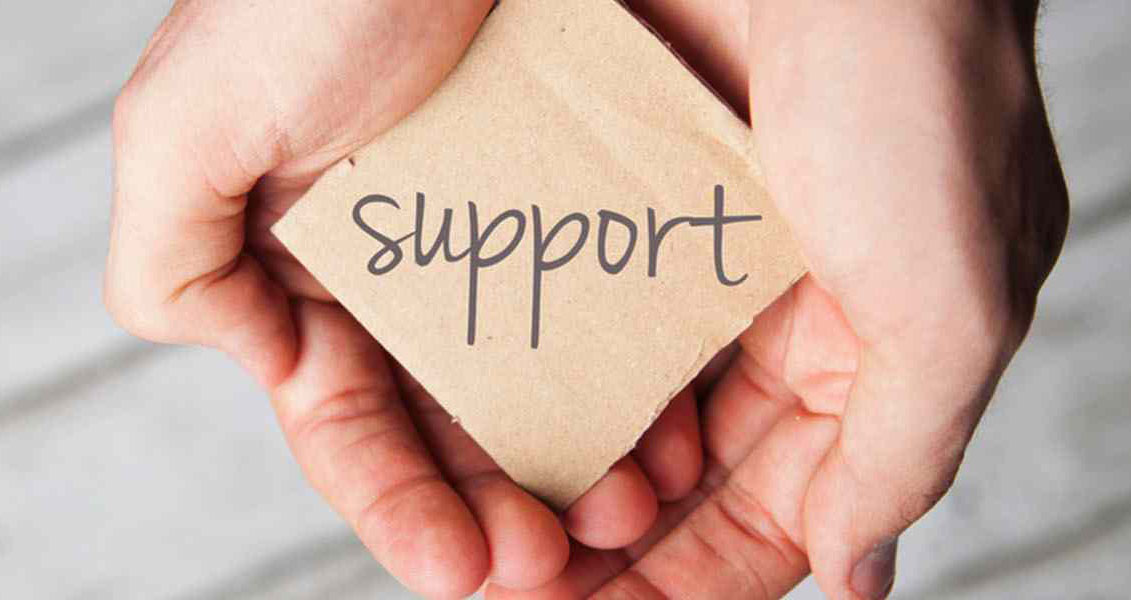 """cupped hands holding a square of paper that reads """"support"""""""