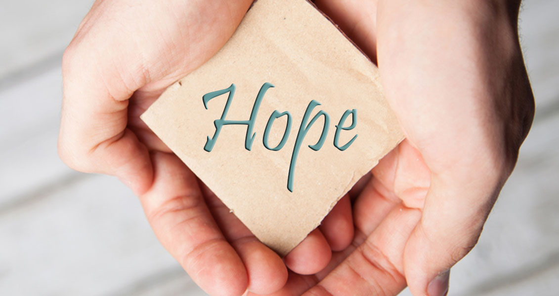 """cupped hands holding a square of paper that reads """"hope"""""""